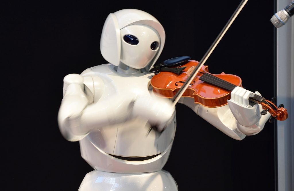 """A violin playing robot, a series of humanoid robots from Toyota Partner Robot, is displayed at a robot event for children in Tokyo on August 9, 2015. The robot event """"Wakudoki (Exciting) Robot Park"""" runs to August 14 at Toyota Motor exhibition showroom Mega Web. AFP PHOTO / KAZUHIRO NOGI (Photo credit should read KAZUHIRO NOGI/AFP/Getty Images)"""